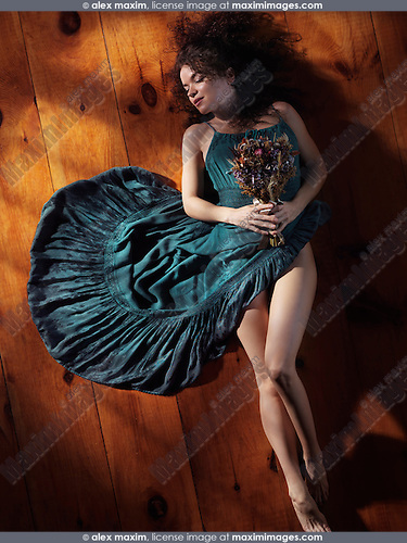 Sensual artistic portrait of a young woman in a green dress with bare legs lying on the floor with closed eyes holding a bouquet of wild flowers