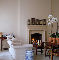 Chinese benches act as coffee tables in front of the cosy fire in this elegant drawing room