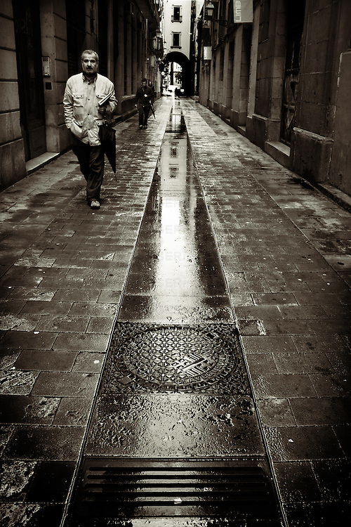 A middle aged man holding an umbrella walking along a wet street