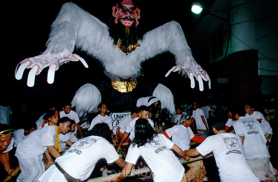 "Eve of Nyepi (Balinese New Year) Festival..An ""Ogoh-Ogoh"" being carried in the big parade...On Nyepi day, evil spirits descend to see wether the island is inhabited by humans. That's why nobody is allowed to leave the house on that day: when the demons don't find anyone, they leave the island alone for another year. Tourists are confined to their hotels, the use of cars is forbidden and, since 2000, even international air traffic is banned..On the eve of Nyepi however, a great ""Pratima"" (town meeting) is held on Denpasar's Puputan Square, complete with Hindu rituals and offerings to the gods. After sunset, huge cardboard monster puppets called ""Ogoh-Ogoh"" mounted on bamboo grids are carried in a loud and vivid parade around town by groups of young men, before they are burnt."