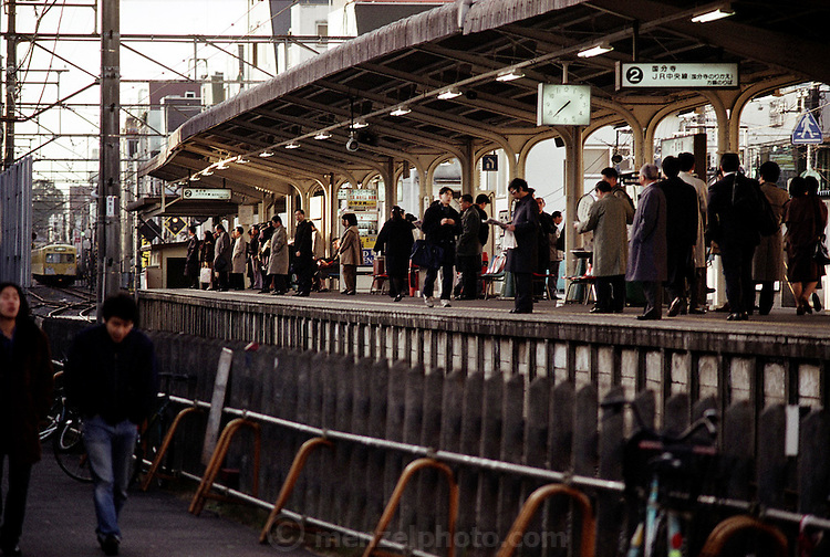 Kazuo Ukita (under the clock on the platform reading the newspaper) and other salary men and women wait for the train to take them to work in, and around, Tokyo, Japan. Published in Material World: A Global Family Portrait, page 51. The Ukita family lives in a 1421 square foot wooden frame house in a suburb northwest of Tokyo called Kodaira City.