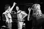 Paul and Linda McCartney Wings Tour 1975. Linda takes a photograph of Paul at the rehearsal studio Elstree. Roadie Trevor Jones talks with Paul.