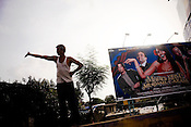 A man is seen waving to passing by traffic in the suburbs of Mumbai.
