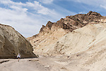 Death Valley National Park, California; a lone hiker amongst views of the multi-colored rock formations seen while walking in the Golden Canyon Trail in late morning sunlight and shadows