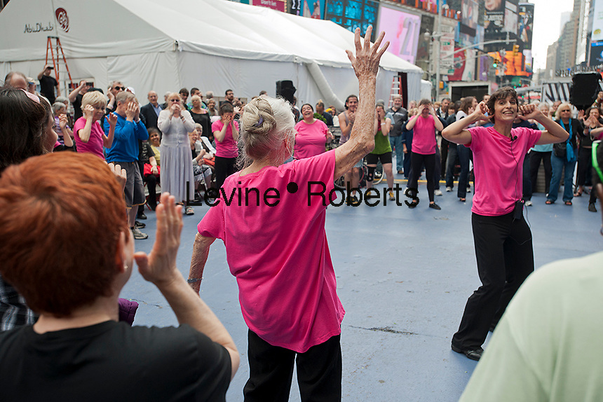 Senior citizens and experienced dancers perform the premiere of ROUNDUP, choreographed by Naomi Goldberg Haas, right, in Times Square in New York on Wednesday, May 16, 2012. Almost a dozen seniors, most from Project FIND's Woodstock Senior Center, with the oldest at 90 years old, performed the piece with other dancers as part of Dances For A Variable Population. The intergenerational project enables older adults to express themselves creatively, interact with a younger population, and engage in physical activity. (© Richard B. Levine)