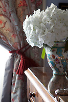 A white hydrangea head has been placed in one of the porcelain vases in the blue bedroom