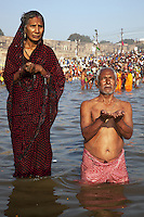 India. Uttar Pradesh state. Allahabad. Maha Kumbh Mela. An Indian Hindu devotee couple takes a holy dip in Sangam. The woman wearing a saree stands up while her husband prays on his knees. The man wears a Janeu which is a consecrated thread worn by each and every Hindu Brahmin of India. The Kumbh Mela, believed to be the largest religious gathering is held every 12 years on the banks of the 'Sangam'- the confluence of the holy rivers Ganga, Yamuna and the mythical Saraswati. In 2013, it is estimated that nearly 80 million devotees took a bath in the water of the holy river Ganges. The belief is that bathing and taking a holy dip will wash and free one from all the past sins, get salvation and paves the way for Moksha (meaning liberation from the cycle of Life, Death and Rebirth). Bathing in the holy waters of Ganga is believed to be most auspicious at the time of Kumbh Mela, because the water is charged with positive healing effects and enhanced with electromagnetic radiations of the Sun, Moon and Jupiter. The Maha (great) Kumbh Mela, which comes after 12 Purna Kumbh Mela, or 144 years, is always held at Allahabad. Uttar Pradesh (abbreviated U.P.) is a state located in northern India. 8.02.13 © 2013 Didier Ruef