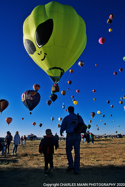 A balloon resembling an alien flies above the young and old alike at the Albuquerque International Hot Air Balloon Fiesta