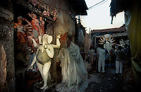 INDIA (West Bengal - Calcutta)  2006, A bylane at kumortuli. Kumortuli in North Calcutta is the hub of Durga idol makers. During the other time of the year the artists engage themselves in prepairing other idols and masks depending on the assignments. But the most of the earning they aquire from making Durga idols. A Durga idol can cost up to 7000 usd. Which is a big price in Indian Currency.  Durga Puja Festival is the biggest festival among bengalies.  As Calcutta is the capital of West Bengal and cultural hub of  the bengali community Durga puja is held with the maximum pomp and vigour. Ritualistic worship, food, drink, new clothes, visiting friends and relatives places and merryment is a part of it. In this festival the hindus worship a ten handed godess riding on a lion armed wth all possible deadly ancient weapons along with her 4 children (Ganesha - God for sucess, Saraswati - Goddess for arts and education, Laxmi - Goddess of wealth and prosperity, Kartikeya - The god of manly hood and beauty). Durga is symbolised as the women power in Indian Mythology.  In Calcutta people from all the religions enjoy these four days of festival in the moth of October. Now the religious festival has become the biggest cultural extravagenza of Calcutta the cultural capital of India. Artistry and craftsmanship can be seen in different sizes and shapes in form of the idol, the interior decor and as well as the pandals erected on the streets, roads and  parks.- Arindam Mukherjee