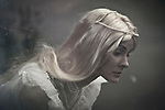A blonde hair lady with big blue sad eyes looking with sad emotion wearing white dress