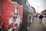 Fans walking past a mural at Seaview Park, Belfast before Northern Irish club Crusaders take on Fulham in a UEFA Europa League 2nd qualifying round, fist leg match. The visitors from England won by 3 goals to 1 before a crowd of 3011.