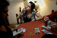 Ceci (centre) smokes as she sits with other tango dancers as they split the tips earned from customers at the end of the night at a restaurant in the El Caminito area of Buenos Aires.