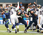 Seattle Seahawks quarterback Russell Wilson (3) passes against the St. Louis Rams during the third quarter at CenturyLink Field in Seattle, Washington on December 29, 2013.  Wilson completed 15 of 23 passes for 172 yards and one touchdown and Lynch rushed for  97 yards, caught one pass for four yards and scored one touchdown in the win. The Seahawks clinched the NFC West title and home-field advantage throughout the playoffs with a 27-9 victory over the St. Louis Rams.   ©2013. Jim Bryant Photo. ALL RIGHTS RESERVED.