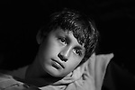 Young boy shot in monochrome vintage Hollywood lighting with shallow depth of field