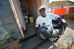 Edith Ncube had polio as a child and today uses a wheelchair. Here she crawls through a doorway of her house in Bulawayo, Zimbabwe. Her wheelchair was provided by the Jairos Jiri Association with support from CBM-US.