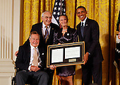 Former United States President George H.W. Bush and U.S. President Barack Obama at a ceremony in the East Room of the White House to present the 5,000th &quot;Daily Point of Life&quot; on July 15, 2013. Left to right: President George H.W. Bush, Floyd Hammer, Kathy Hamilton, and President Obama. <br /> Credit: Dennis Brack / Pool via CNP