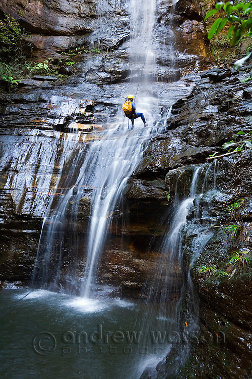 An abseiler descends a waterfall in the Valley of the Waters.  Katoomba, Blue Mountains, New South Wales, AUSTRALIA