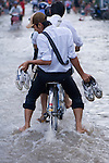 Teenagers ride through flooding from the Can Tho River along the Mekong Delta, Southern Vietnam