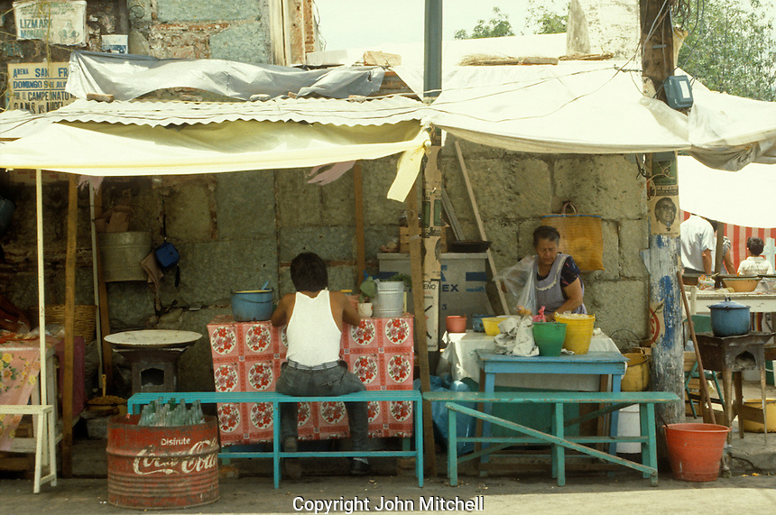 Man eating lunch at an outdoor food vendor's stall in the city of Oaxaca, Mexico