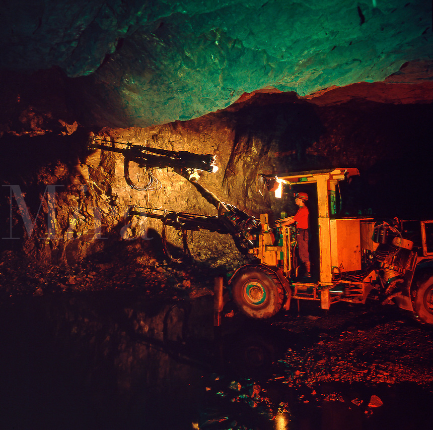 Twin turret mobile drilling machine working in underground copper mine..