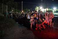 BENIC&Agrave;SSIM, SPAIN - English festival goers queue for taxis taking them away from the festival site. ..Described by some as a Mediterranean Glastonbury, the Festival Internacional de Benic&agrave;ssim (FIB) is the largest music festival outside the UK to target British visitors. In 2010, seven of the eight main headline slots were filled by English bands...A small coastal town of 13,000 inhabitants, Benic&agrave;ssim hosted some 200,000 visitors in 2009, with 40% of those believed to be coming from the UK. In 2010, attendances fell to 127,000 visitors but the percentage of UK visitors is believed to have risen.