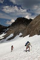Backpackers climbing snow slope, Bailey Range Traverse, Olympic Mountains, Washington