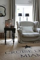 There is a retro feel to this corner of the living room; the side table and mirror are both antique and the vintage armchair has been recovered in grey linen