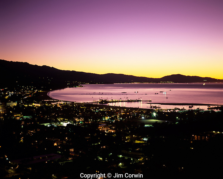 Santa Barbara at sunrise with city lights along the Pacific Ocean beach with Stearns Wharf and Santa Ynez Mountain Range in background, Santa Barbara, California USA..