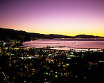 Santa Barbara at sunrise with city lights along the Pacific Ocean beach with Stearns Wharf and Santa Ynez Mountain Range in background, Santa Barbara, California USA..