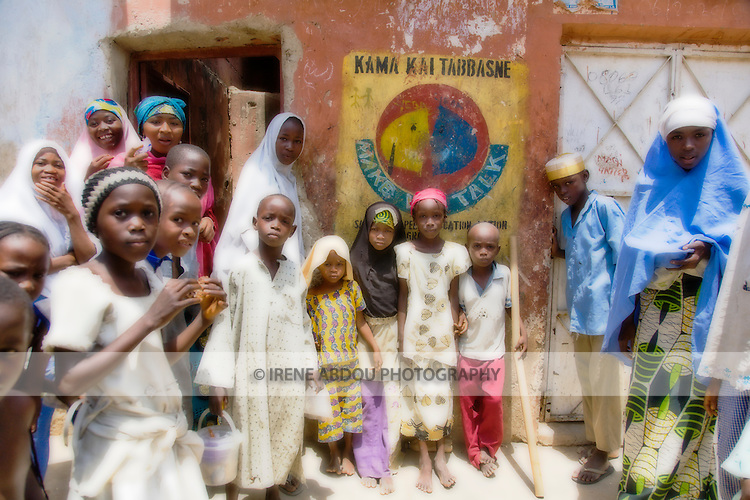 Women and children in the Gyadi-Gyadi area of Kano, Nigeria gather around the foreigner with the camera in curiosity.