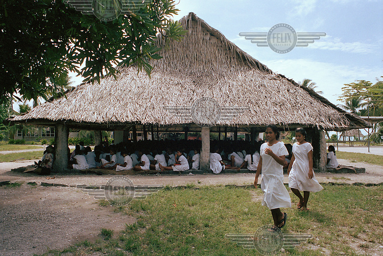 A service in the maneaba (community meeting house) at Stephen Whitmee High School. The building was constructed in a traditional manner using coconut and pandanus materials. The school assembly, church services and all other ceremonial and formal occasions are held in the maneaba.