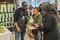 A worker assists a shopper in the new Whole Foods Market in Newark, NJ on opening day Wednesday, March 1, 2017. The store is the chain's 17th store to open in New Jersey. The 29,000 square foot store located in the redeveloped former Hahne & Co. department store building is seen as a harbinger of the revitalization of Newark which never fully recovered from the riots in the 1960's.  (© Richard B. Levine)