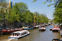 Tourist boat on sightseeing cruise tour along the canal district in the Jordaan area of Amsterdam, The Netherlands