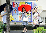 Passersby takes a photo of the ruling Liberal Democratic Party headquarters while standing in front of posters of local constituency candidates ahead of Japan's elections in Tokyo, Japan on Sunday 30 August 2009..Photographer: Robert Gilhooly