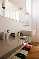 The long stone washstand in the bathroom creates the perfect storage space for shoe boxes underneath