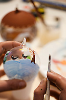 A glass bauble is being painted with a wintry scene