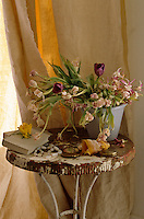 A vase of wilting tulips is displayed on a distressed metal table against a natural linen curtain