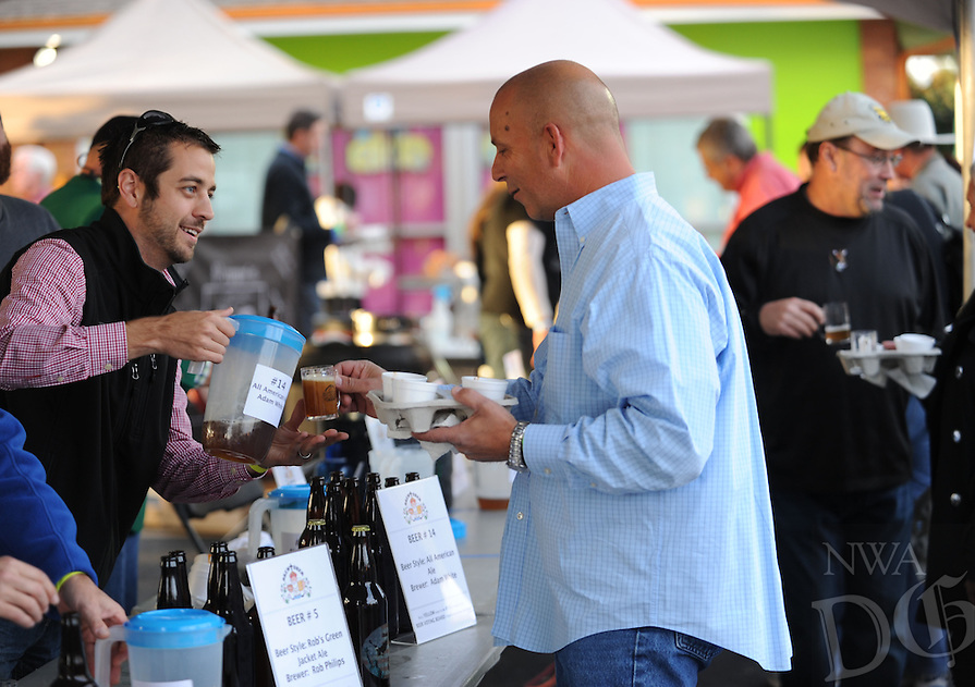 NWA Democrat-Gazette/ANDY SHUPE<br /> Adam White (left) smiles Saturday, Oct. 17, 2015, as he pours a sample of his home-brewed ale for Greg Ferus of Springdale during the second St. Raphael Catholic Church Brewtober Chilifest in Springdale. The event gave attendees the chance to taste home-brewed beers and ciders and sample chili with awards going to the two winners as determined by a popular vote.