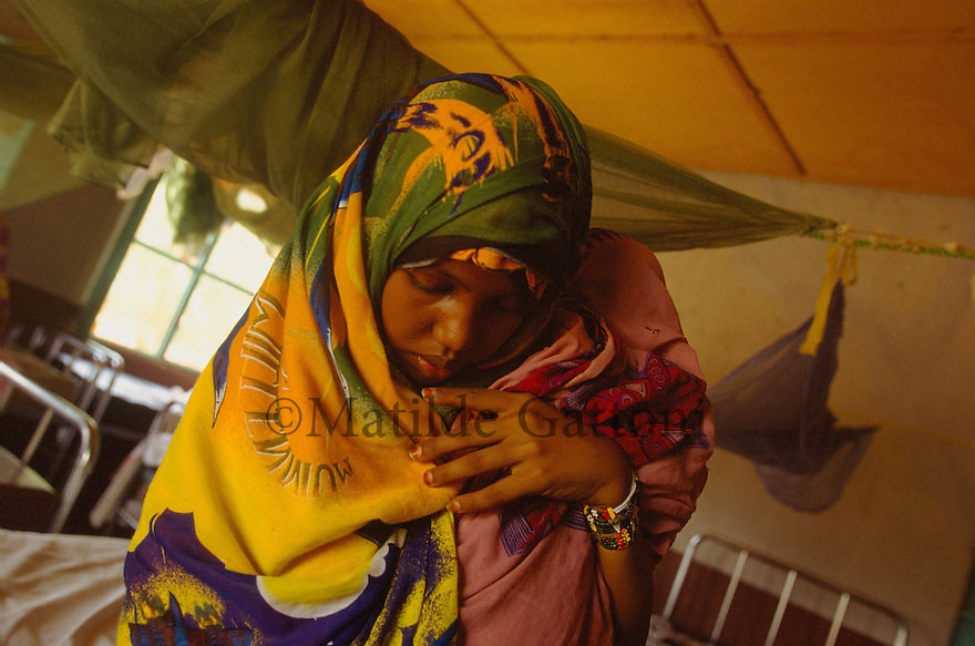 Eritrea - Gash Barka - Mother taking care of her child in an hospital. As a result of 30 years of war for independence against Ethiopia (from 1961 to 1991) and another 3 years from 1997 to 2000, there are 50,000 Eritreans currently living in internally displaced (IDP) camps throughout the country. These IDPs have fled three times in the last 10 years, each time because of renewed military conflict. They lived in relatives' homes when lucky enough, but mostly, the fled to the mountains, where they attempted to do what Eritreans do best, survive. Currently there is no Ethiopian occupation in Eritrea, but landmines prevent the IDPs from finally going home. .It is estimated that every Eritrean family lost two or three members to the war which makes the reality of the current emergency situation even more painful for Eritreans worldwide. Currently, the male population has been decreased dramatically, affecting the most fundamental socio-economic systems in the country. Among the refugee population, an overwhelming majority of families are female-headed, severely affecting agricultural production. For, IDPs in particular, 80% of households are female-headed..The unresolved border dispute with Ethiopia remains the most important drawback to Eritrea's socio-economic development, as national resources (human and material) continue to be prioritized for national defense. Eritrea is vulnerable to recurrent droughts and variable weather conditions with potentially negative effects on the 80 percent of the population that depend on agriculture and pastoralism as main sources of livelihood. The situation has been exacerbated by the unresolved border dispute, resulting in economic stagnation, lack of food security and increased susceptibility of the population to various ailments including communicable diseases and malnutrition..