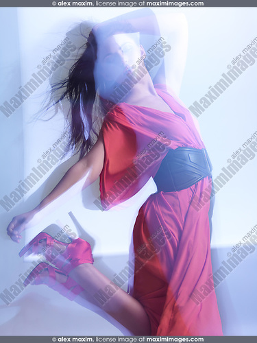 Futuristic dynamic high fashion photo of a young woman in a red dress posing in shiny neon light settings. The photo was not digitally manipulated.