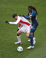 Keon Daniel (26) of the Philadelphia Union fights for the ball with Juan Carlos Toja (7) of the New England Revolution during the game at PPL Park in Chester, PA.  The Philadelphia Union defeated the New England Revolution, 1-0.