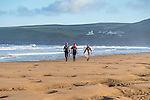 Surfers on the beach at Croyde Bay, North Devon.