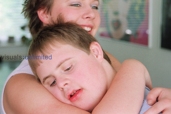 Teenage girl hugging brother with Downs Syndrome smiling.  MR