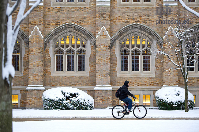 December 9, 2011; A student rides past Biolchini Hall of Law. Photo by Barbara Johnston/University of Notre Dame.