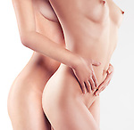 Closeup of nude bodies of two young naked woman embracing isolated on white background