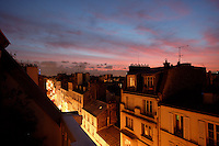 Montmartre, Paris, France. A high angle view over the city rooftops at dusk. Far below the street lights shine whilst all is quiet at chimney level beneath the pink and blue evening sky. Picture by Manuel Cohen