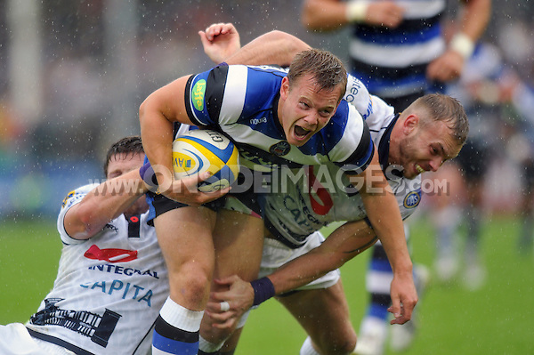 Chris Cook is double-tackled in possession. Pre-season friendly match, between Bath Rugby and Bristol Rugby on August 17, 2013 at the Recreation Ground in Bath, England. Photo by: Patrick Khachfe / Onside Images