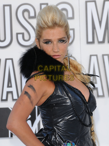 KESHA (Ke$ha aka Kesha Rose Sebert) .at The 2010 MTV Video Music Awards held at Nokia Theatre L.A. Live in Los Angeles, California, USA, .September 12th 2010..Arrivals Vmas half length black dress leather plait long hair braid fur collar bow ribbon beads quiff  cross earring make-up.CAP/RKE/DVS.©DVS/RockinExposures/Capital Pictures.