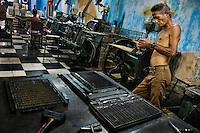 A Cuban master printer, leant against a printing machine, waiting for a new load in the state print shop, Santiago de Cuba, Cuba, 4 August 2008.