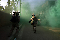 Iraq: Ramadi: June 30, 2006: US Marines of the 3-8 Weapons Company run through a street filled with green smoke, after searching a building in Ramadi for suspected insurgents.